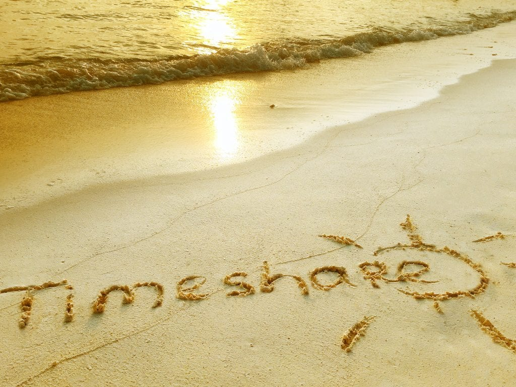 Timeshare written in the sand on a beach