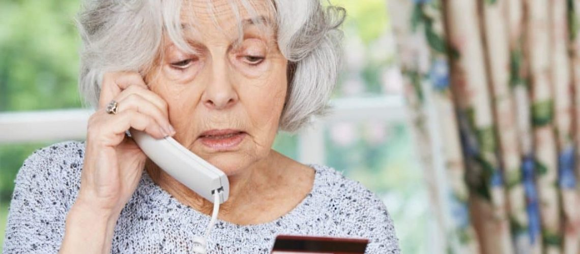 Senior Woman Giving Credit Card Details On The Phone to Timeshare Scam Company