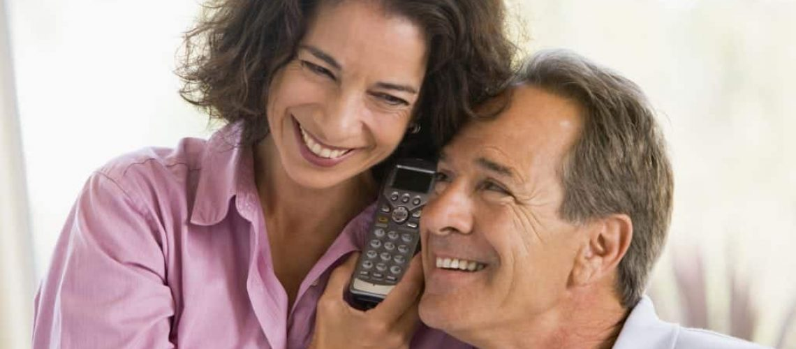 Couple indoors using telephone to talk to timeshare solicitors