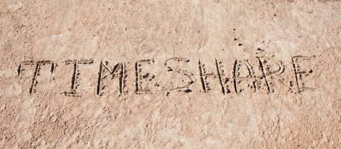 a beach with timeshare written in the sand